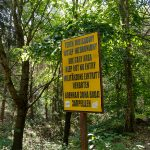 A yellow sign in the woods, prohibiting trespassing near the military ruins close to Dębina, Poland.