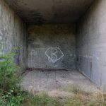 Looking in a small concrete hall with graffiti at military ruins near Dębina, Poland.