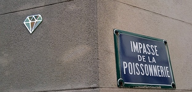 Diamond shaped mirror street art mounted to a wall at Impasse de la Poissonnerie, Le Marais, Paris